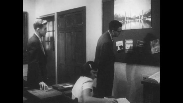 1950s: Teacher and observer walk around classroom and speak. Boy leans into doorway of classroom and speaks.