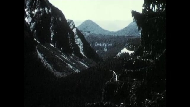 1950s: Valley.  Mountains.  Cars drive down road.