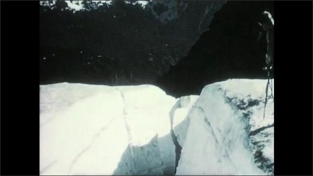 1950s: Glacier.  Man stands next to crevasse.