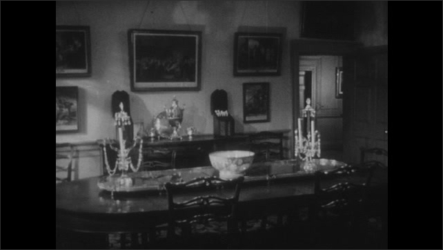 1950s: Colonial dining room. Candelabras and silver service on dining table and fireplace. Painting of George Washington.
