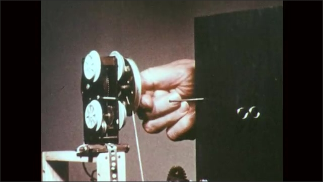 1970s: UNITED STATES: hands wind up motor and cord. Fingers reposition string in experiment
