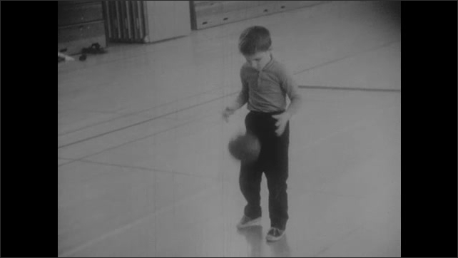 1960s: UNITED STATES: girl bounces ball on gym floor. Boy bounces ball on floor. Boy throws ball against wall.