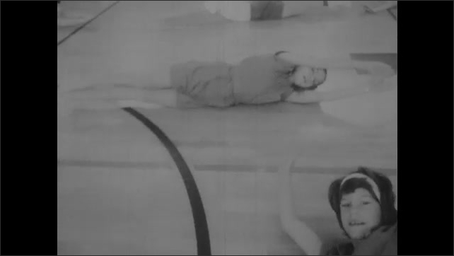 1960s: UNITED STATES: children repeat movements in task. Foundations of movement. Children roll on floor.