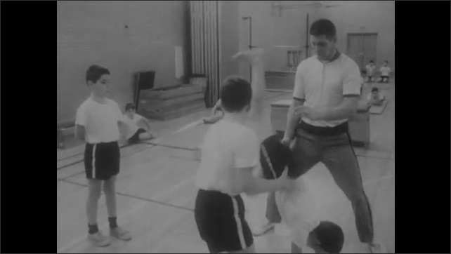 1960s: UNITED STATES: children work in threes. Cooperative effort and assistance. Spatial awareness. Children hold hands and support each other.