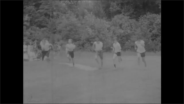 1960s: UNITED STATES: boys play soccer on grass. Boys in running race.
