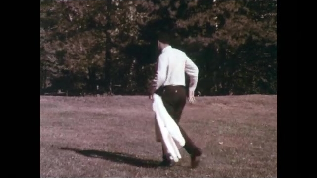 1970s: Apple rolls on grass. Boy throws apple back to the man. The boy and man look at each other angrily. Man walks away. Boy watches him sadly.