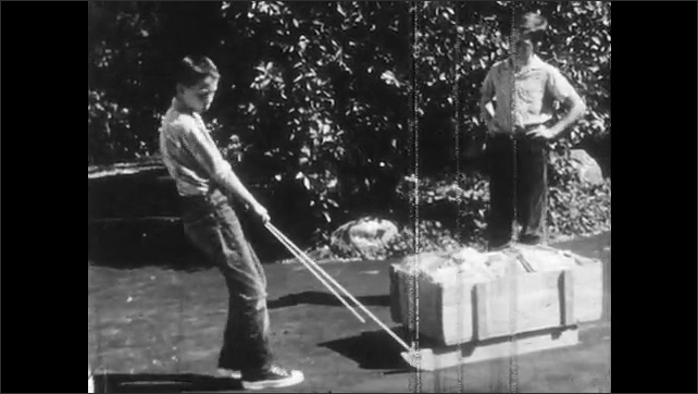 1950s: Wooden sled and ropes appear. Box of comics appears atop wooden sled. Boy pulls sled along driveway. Sled runners slide on pavement.