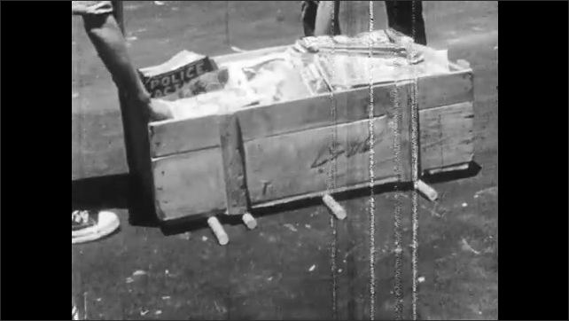 1950s: Man rolls metal drum along pavement. Boys pull  box of comics across pavement with dowel rods. Boys and dowel rods disappear from box of comics.