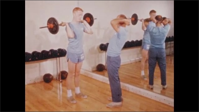 1960s: UNITED STATES: astronauts lift weights in gym. Astronauts work out with weights. Astronaut in training