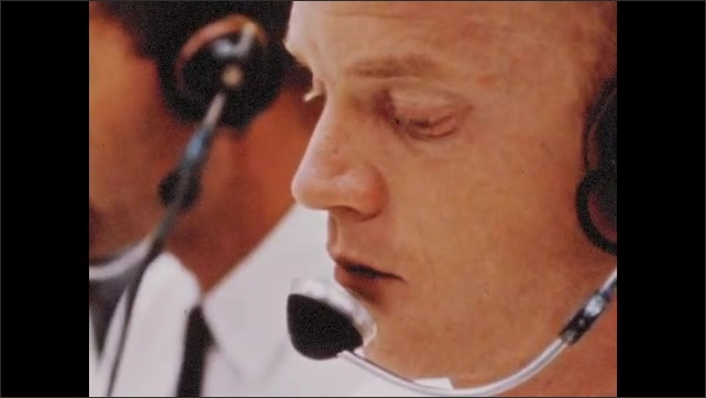 1960s: UNITED STATES: astronaut with headset. Astronaut sits at desk in ground control room