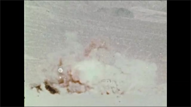 1970s: UNITED STATES: bombs drop on ground. Soldier loads missiles. Plane fires torpedo. Explosion on ground