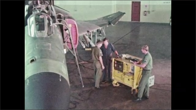 1970s: UNITED STATES: Air force students test electrical equipment. Multi weapon system checks with machine. Students talk to presenter. Empty cartridges on conveyor