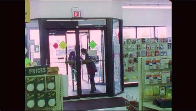 1990s: Man and woman enter pet store. Man turns and walks down aisle. Woman stands near doors and looks around.