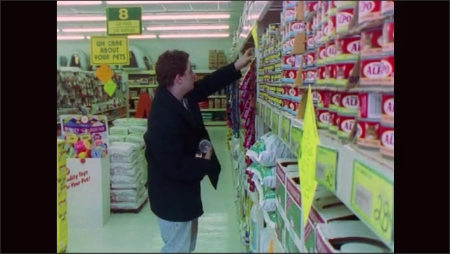 1990s: Man approaches shelves of pet food. Man retrieves cans of ped food. Man carries pet food cans through store.