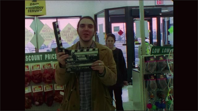 1990s: Woman and man flee from store. Filmmaker claps slate and speaks. Woman runs through store and speaks to man. Filmmaker claps slate and speaks.