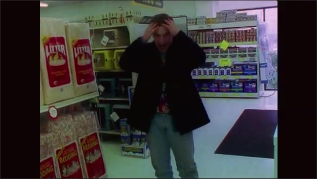 1990s: Man stands in pet store with arms full of pet food cans. Filmmaker claps slate and speaks. Man drops pet food cans onto floor. Pet food cans on floor. Man stares with mouth agape.