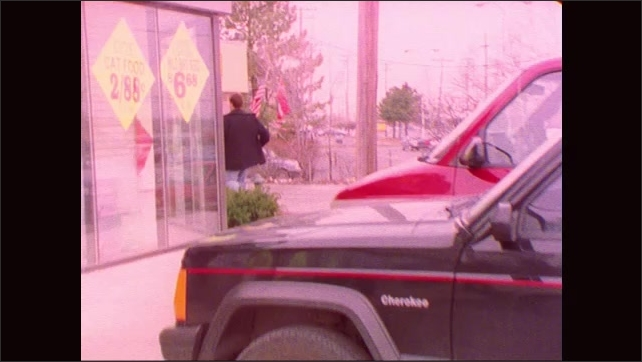 1990s: Exterior signage of pet store. Man bursts through entrance of pet store and runs around side of store. Man runs out of pet store.