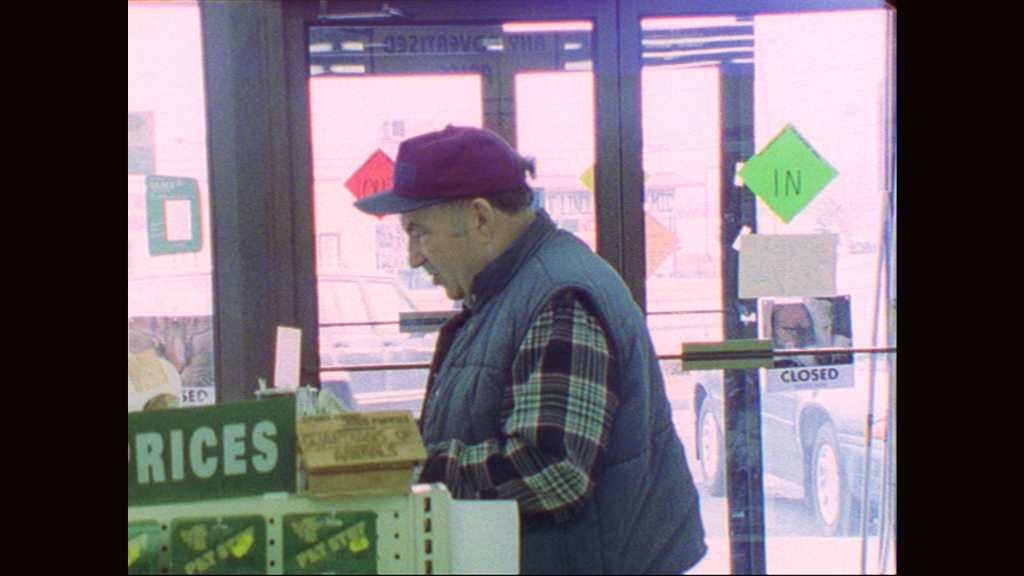 1990s: Man stands at check out counter of store. Man and woman stand outside store entrance. Man opens doors and enters department store. Man walks through department store.