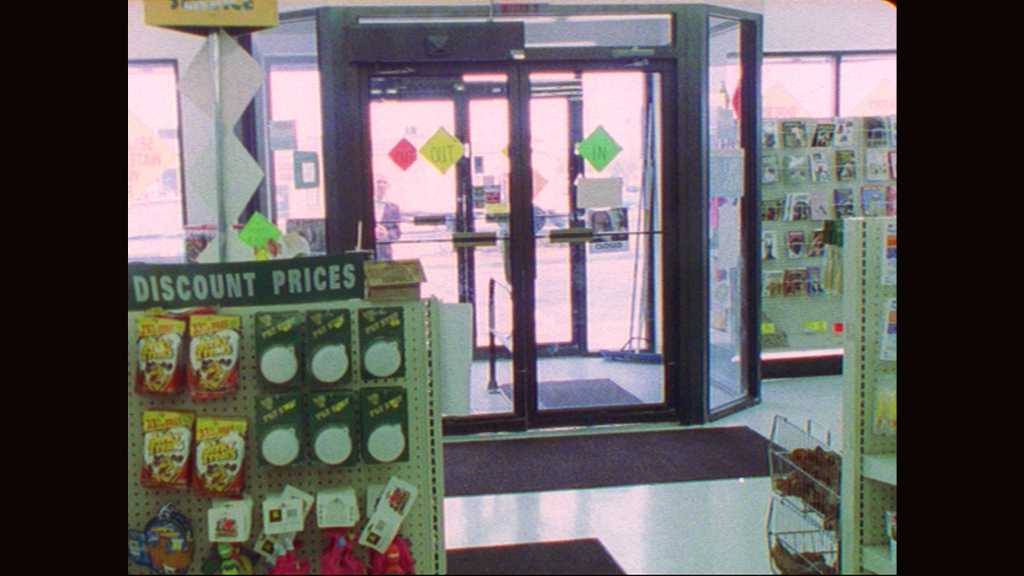 1990s: Men and women outside store entrance look in through doors. Man with slate speaks in front of store exit. Man marks slate and ducks behind store display.