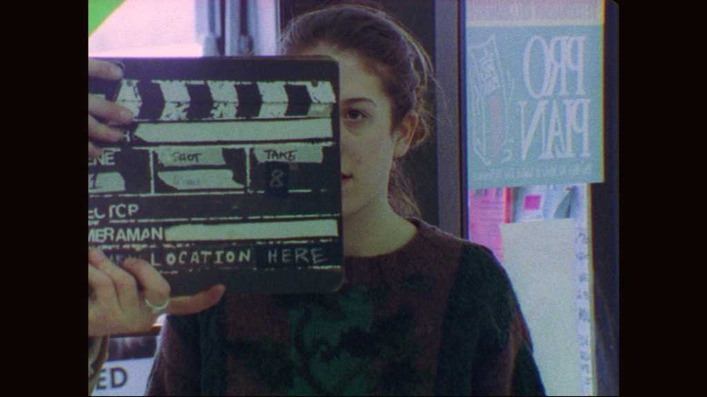 1990s: Hands hold film slate in front of woman. Hands clap film slate. Woman speaks. Hands hold film slate in front of woman. Hands clap film slate. Woman speaks.