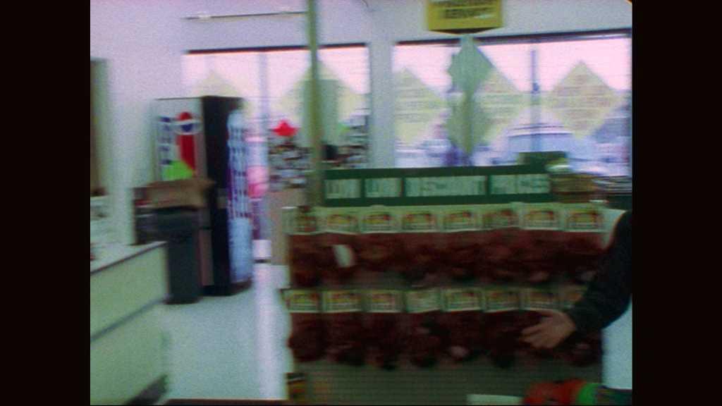 1990s: Man runs past woman. Filmmaker wipes brow. Filmmaker claps slate and speaks. Man shoves past woman and customers. Man and woman run out of pet store.
