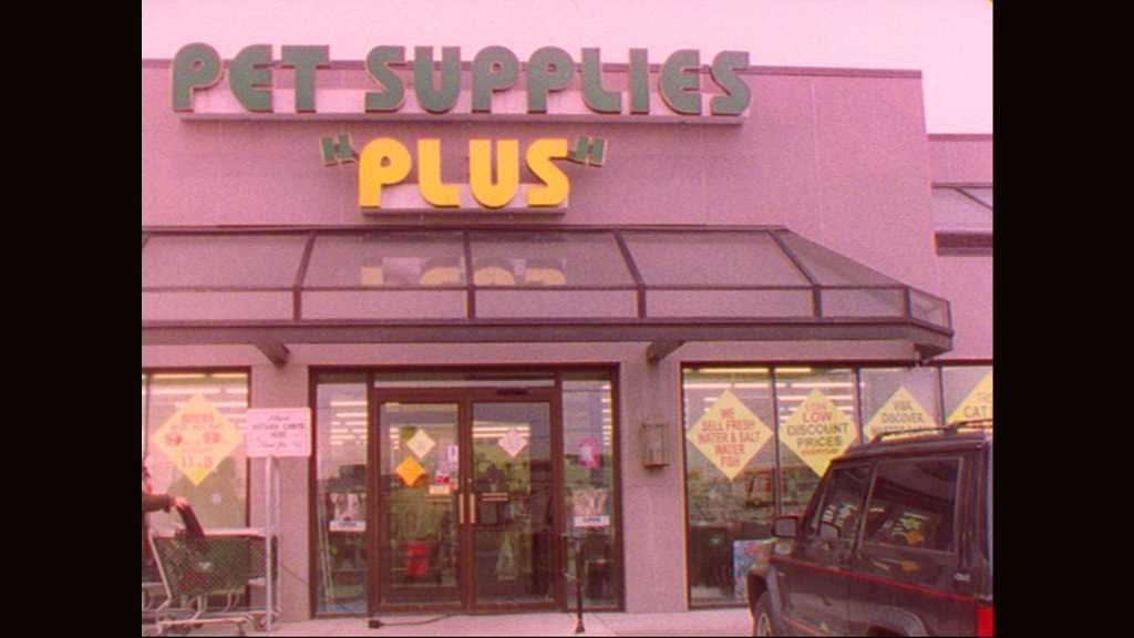 1990s: Elderly man exits pet supply store and walks past parked cars. Elderly man with bag enters pet supply store.