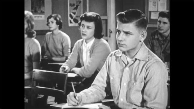 1950s: Teacher addresses class. Children look and write