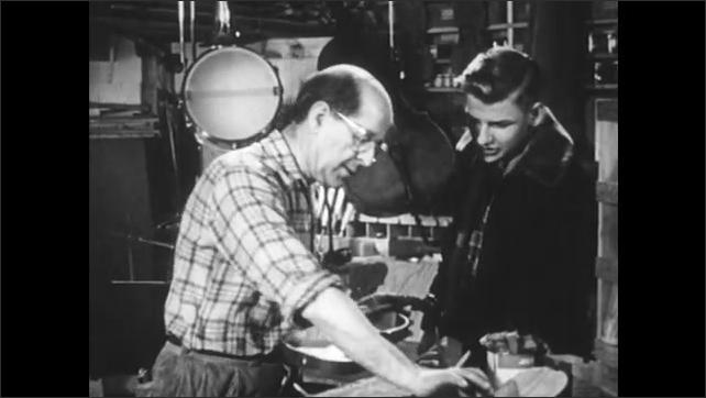 1950s: Boy watches man assemble violin. Men around music player