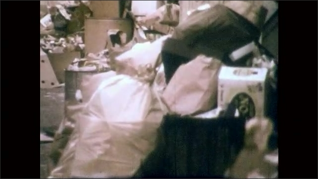 1970s: Pile of garbage including boxes and bags. Tied garbage bags fluttering in wind.