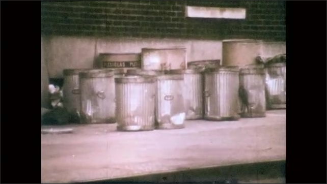 1970s: Plastic garbage bins on side of road. Trash cans next to stairs.Trash cans on sidewalk. Stack of empty trash cans. Rows of empty trash cans.
