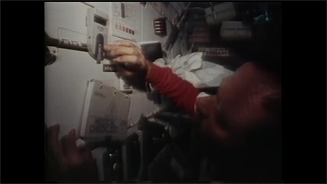 1990s: Astronauts perform experiments in space craft.