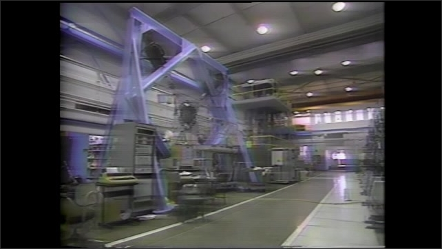 1990s: Man walks through large research facility. Woman walks up to spacecraft, puts on headphones.
