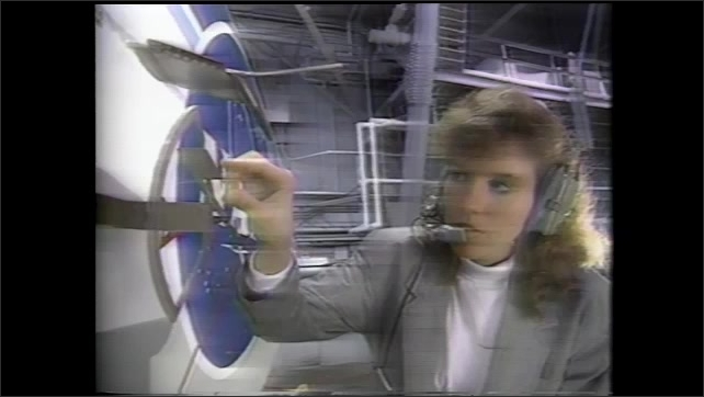 1990s: Woman wears headset, talks. Woman adjusts metal pieces on side of aircraft.