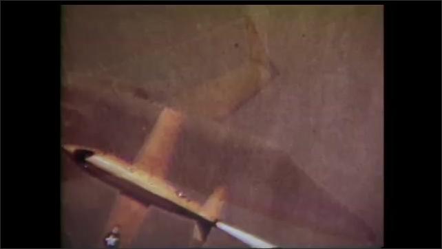 1990s: Bi plane flies low over ground. Airliner flies on the sky. Fighter jet flies. Man assembles model aircraft.