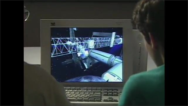 2000s:Scientists look at computer monitor which displays a zoomed in shot of the ISS spaceship as an animation.
