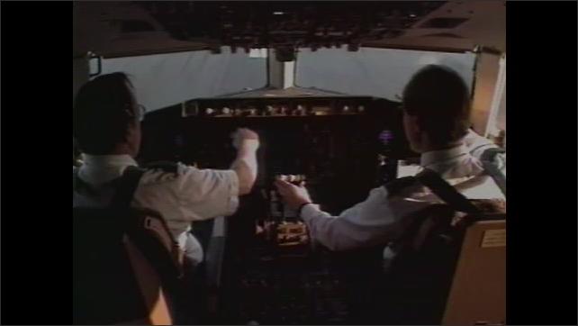 1990s: Interior of cockpit, pilots flying plane. Plane taking off.