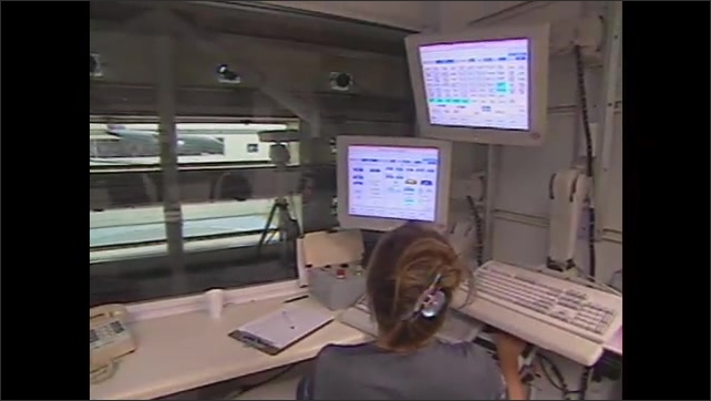 1990s: Close up of monitor, zoom out to woman looking at monitors.