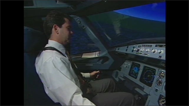 1990s: Zoom out on flight simulator. Man sitting in simulator.