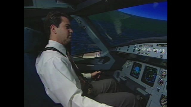 1990s: Gears moving under flight simulator. Man sitting in simulator. Hand adjusts controls. Man presses button. Man in simulator. View over man's shoulder, view of screen. Simulator moving.