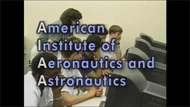 1990s: High angle pan across tents. Plane flies past control tower. Men in control tower. Kids at computers, title on screen. Zoom out on kids at computers. Kids in computer lab.