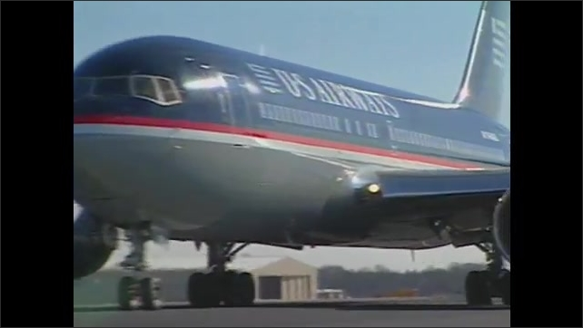 1990s: Man in control tower. Pilot in cockpit. Animation of airport. Plane landing on runway. Plane at airport. Woman and boy in plane, talk into camera. People boarding trolley. Trolley driving.