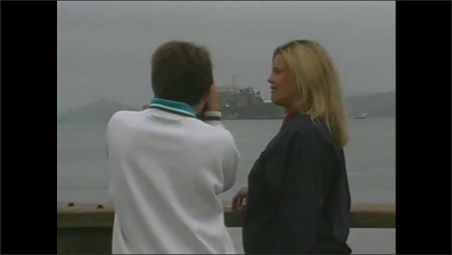 1990s: Sped up footage, woman and boy on street, in market, look at produce. Woman and boy look at boats, look through viewer. Golden Gate bridge, pan to woman and boy, woman talks into camera.