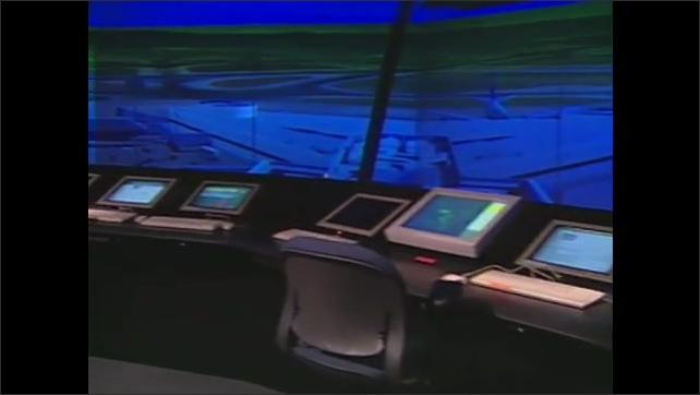 1990s: Pan across screens in control tower. Men at computers. Man at computer.