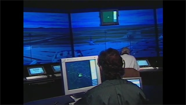 1990s: Man at computer. Men in simulated control tower. Animation of planes on runway. Cars on highway.