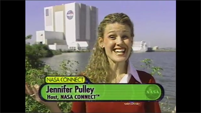 2000s: UNITED STATES: NASA Connect title. Lady talks to camera. NASA building in Florida. Vehicle Assembly Building