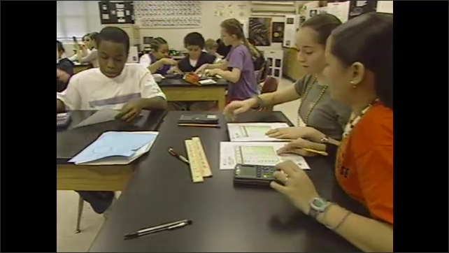2000s: UNITED STATES: astronomical unit measurement. Students work at desks. Student with toilet roll sheets.