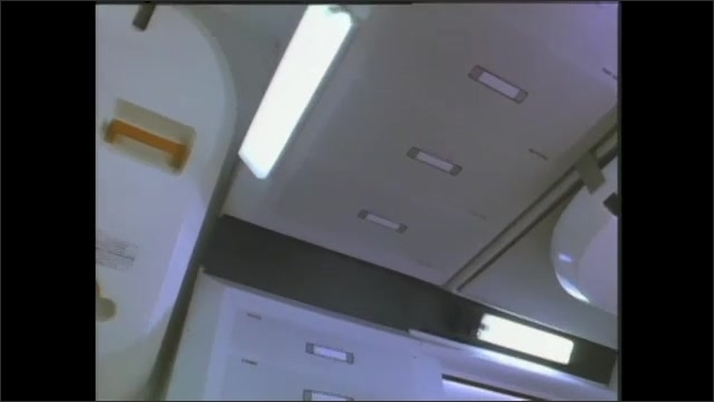 1990s: female astronaut looks at computer monitor, male astronaut floats above as stars show through window