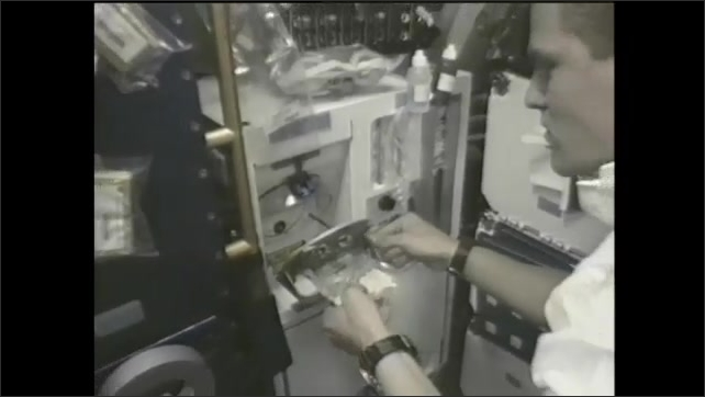 1990s: man in front of lab equipment pulls out and examines sample encased in plastic