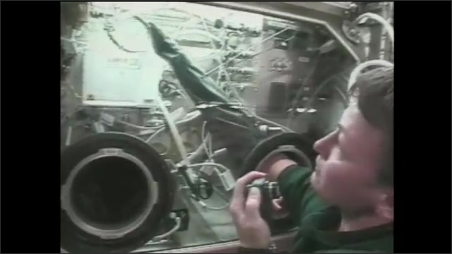 1990s: female astronaut inserts hand into glove attached to chamber while talking, large forceps float in the chamber