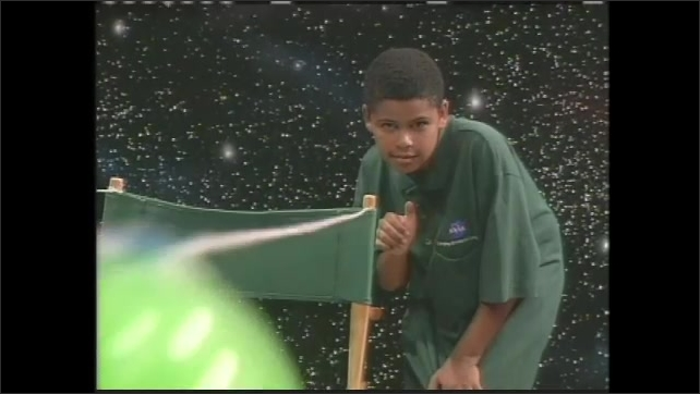 1990s: boy and girl release balloon taped to string, balloon shoots away, girl smiles and is surprised, they blow up balloons, boy winds propeller on toy plane, releases plane from desk with KSNN logo